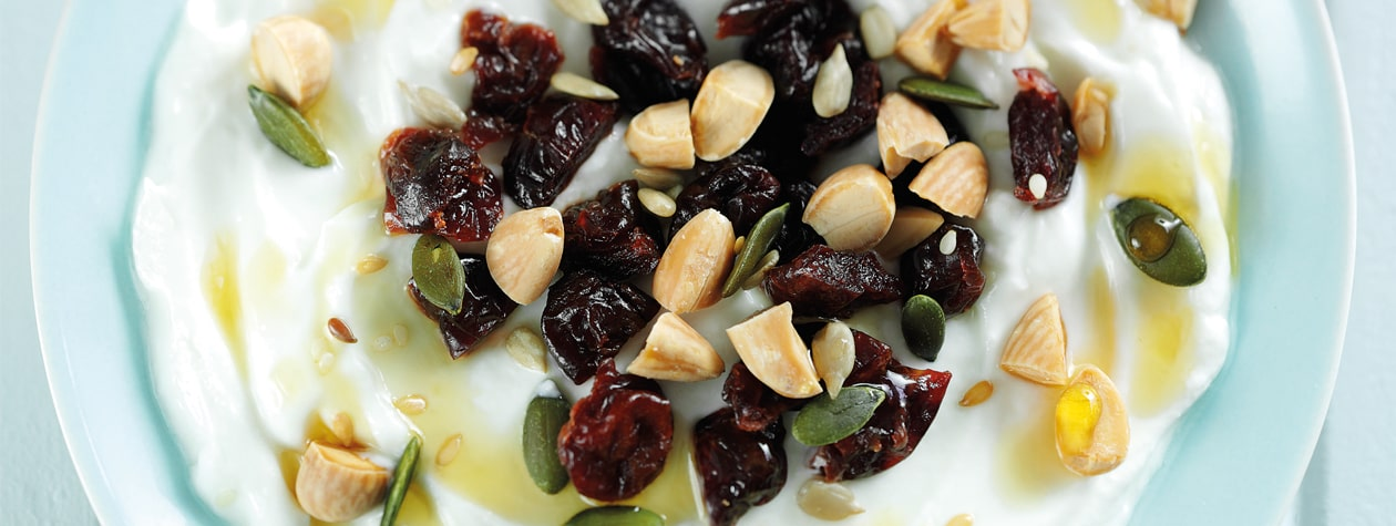Yoghurt topped with Dried Cherries, Almonds & Seeds & drizzled with Maple Syrup